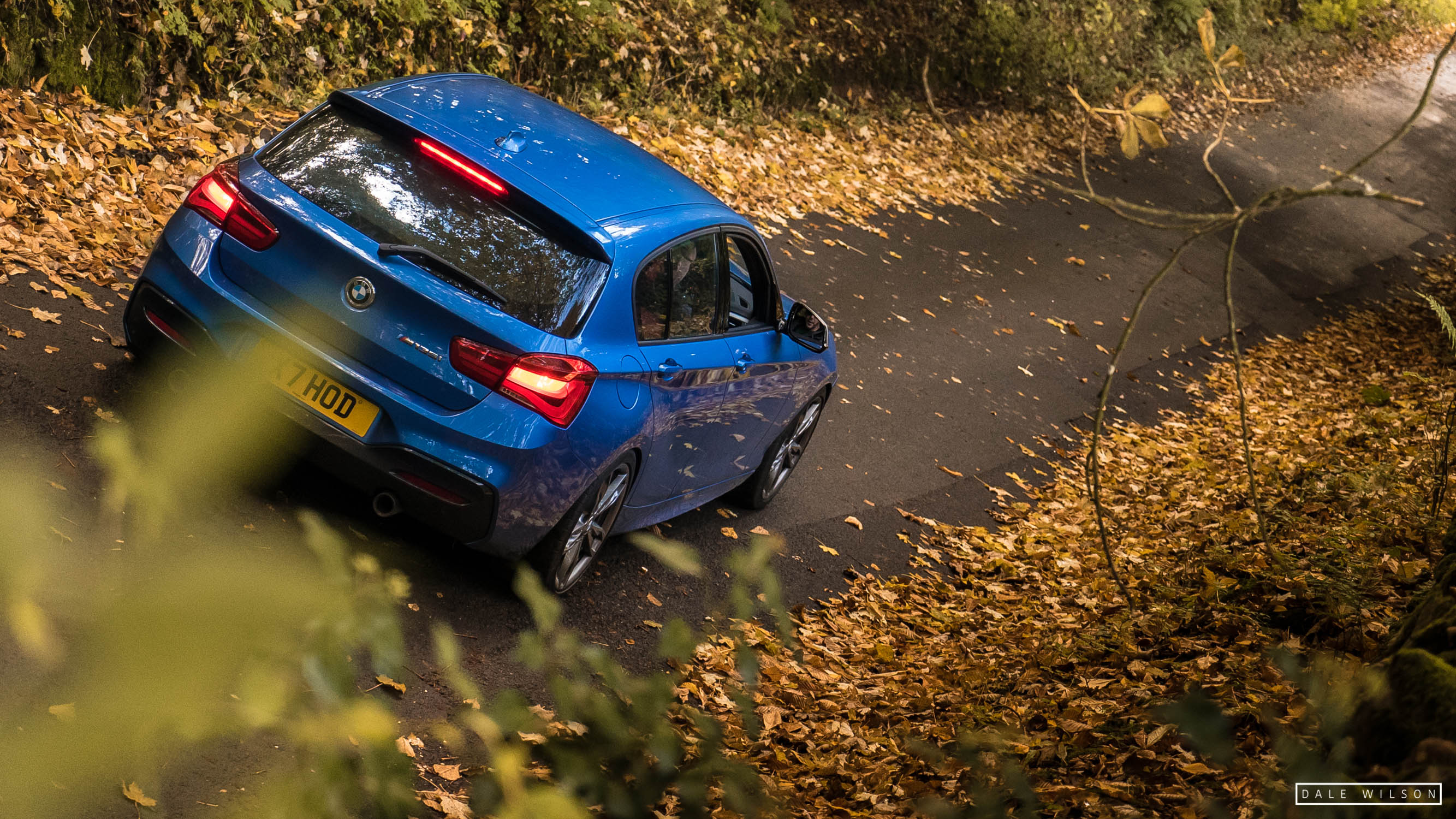 An Estoril blue BMW 135i in autumn leaves cumbria