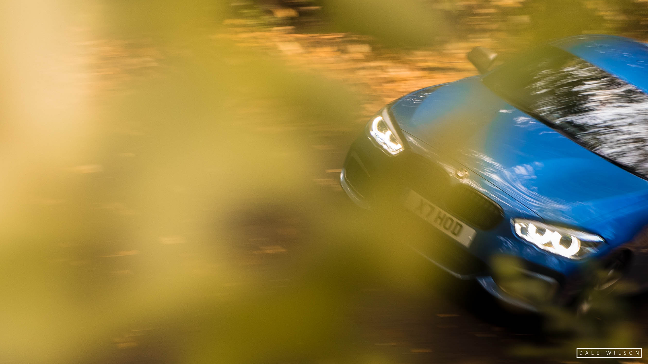 An Estoril blue BMW 135i in autumn leaves cumbria panning shot