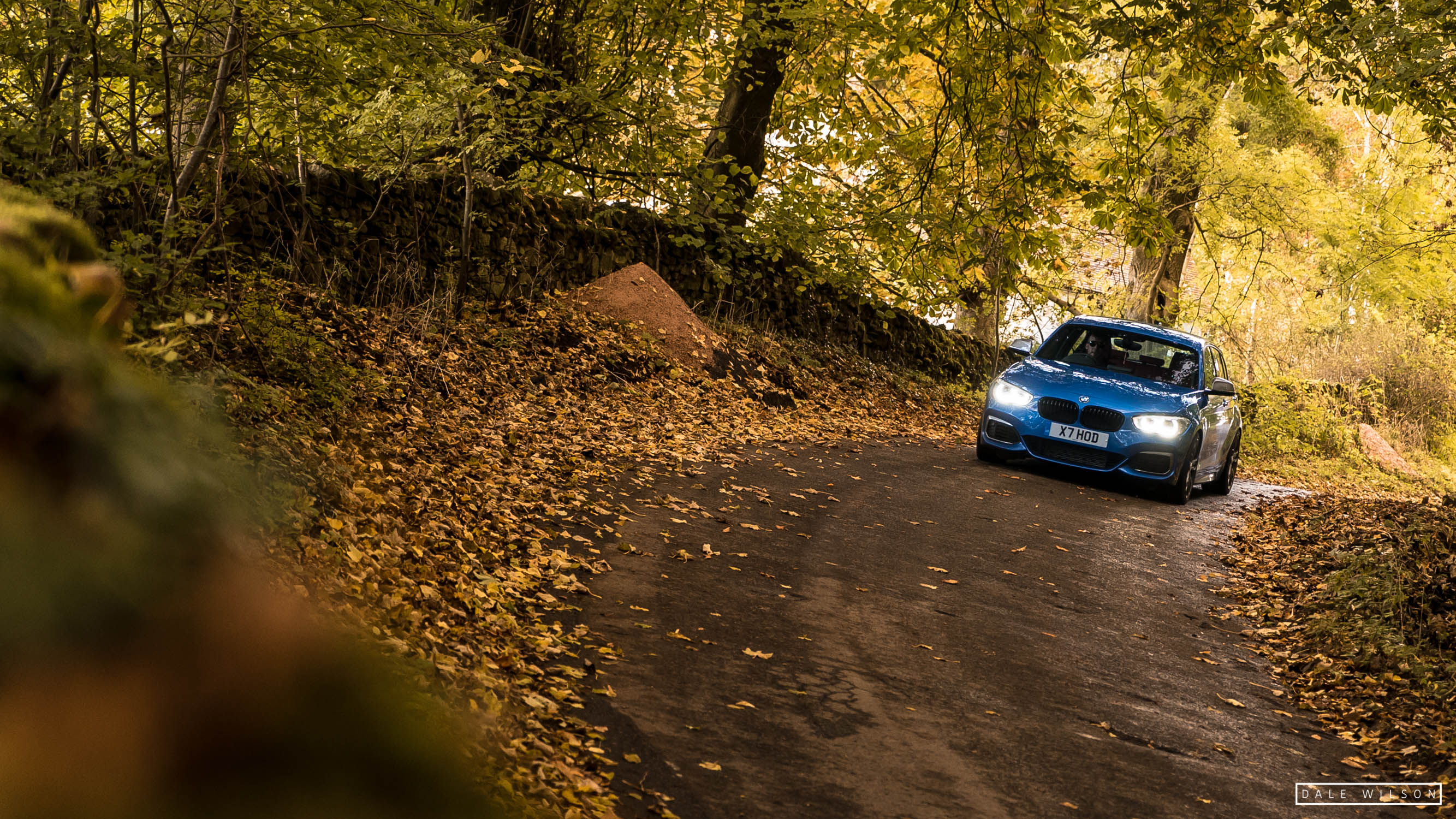 An Estoril blue BMW 135i xenon headlights in autumn leaves cumbria