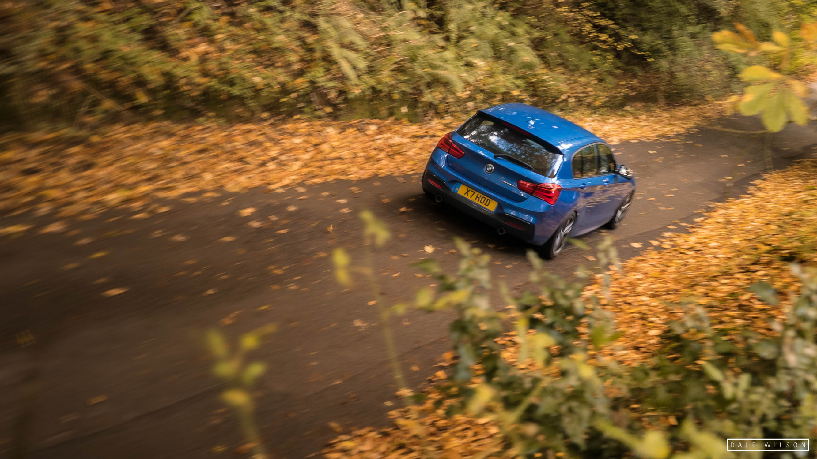 Panning shot of an Estoril blue BMW 135i in autumn leaves cumbria